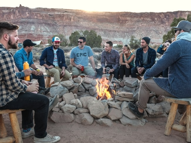 Groep rondom kampvuur tijdens groepsreis
