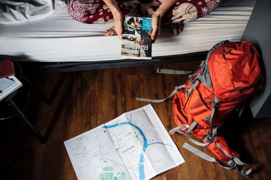 Meisje op bed controleert haar koffer aan de hand van checklist voor kamperen