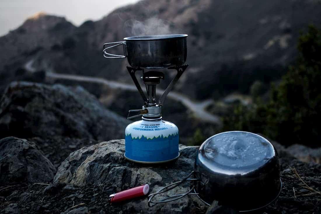 Kampeerrecepten koken op een gasstel in de bergen